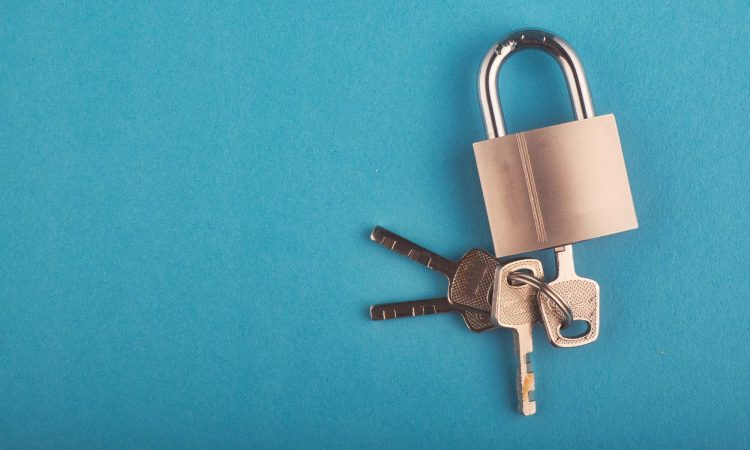 locked Padlock and bunch of key on the blue background.copy space for text